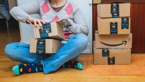 PARIS, FRANCE - JAN 13, 2018: Woman next to stack of Amazon Prime packages delivered to a home door impatient unboxing unpacking