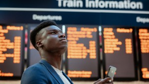 A,Businessman,Looking,Up,In,A,Train,Station,While,Holding