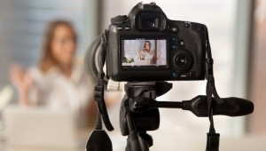 Close,Up,Image,Of,Camera,On,Tripod,With,Smiling,Woman