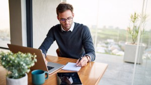 Young businessman sitting at a table at home working on a laptop and writing notes down on a notepad