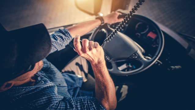 Semi Truck Driver Making Conversation with Other Truck Drivers Through CB Radio.